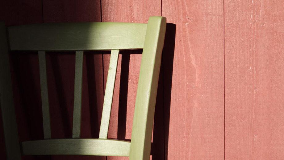 Chaise adossé à un mur en bois rouge